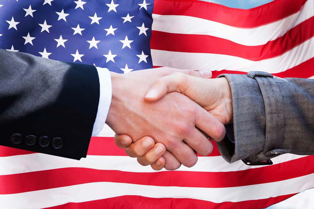 american flag with 2 people shaking hands